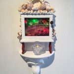 Out of balance, 2017, 37x25x12, repurposed wooden box, velvet, oil on glass, shells, faux pearls, LED lights, napkin ring, fimo, brass knob