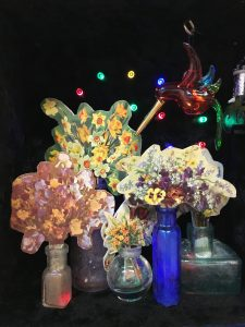 Spring flowers are waning, 2017, 35x22x17, repurposed wooden box, velvet, glass bottles, paper on wood, wind up music box, old glass figurine, repuposed doily, wool, LED lights